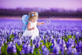 stock photo of fairies  - Portrait of an adorable toddler girl in a magic fairy costume and flower crown in her curly hair playing with a wand in a beautiful field of purple hyacinths in Keukenhof Holland on windy spring day - JPG