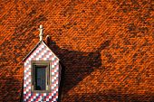 foto of red roof tile  - Red tile roof with a tower with a square texture in the center of Bratislava Slovakia closeup - JPG