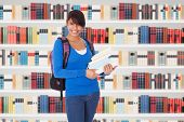 stock photo of book-shelf  - Young College Student Girl In A Library With Books In Front Of Book Shelves - JPG