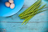 stock photo of dingy  - Natural white eggs in a blue bowl and Spring onions over dingy blue wooden table - JPG