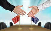 pic of minister  - Two diplomats from China and Australia extending their hands for a handshake on an agreement between the countries - JPG