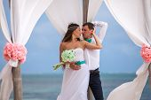 picture of wedding arch  - young loving couple on their wedding day beautiful wedding arch on beach outdoor beach wedding in tropics - JPG