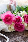 stock photo of mother-of-pearl  - fresh pink  rose flower on lace with gift box  and pearls  - JPG