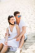 image of couple sitting beach  - Young couple sitting on a sand beach - JPG