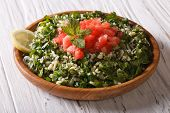 image of tabouleh  - Tabbouleh salad closeup in a wooden bowl on the table - JPG