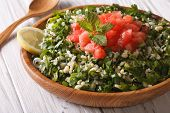 picture of tabouleh  - Dietary eastern Tabbouleh salad closeup in a wooden bowl. Horizontal ** Note: Shallow depth of field - JPG