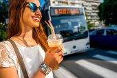 picture of walking away  - Young woman walking on the street with take away coffee  in the transparent cup in the city - JPG