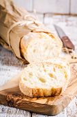 picture of french culture  - French Baguette on cutting board on white rustic table - JPG
