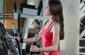 pic of cardio  - Young beautiful athletic girl on warming up on the cardio trainer. ** Note: Shallow depth of field - JPG