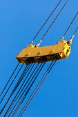 stock photo of pulley  - Large yellow pulley assembly with three sets of pulleys and tightly stretched diagonal steel cables above and below - JPG