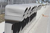 picture of mailbox  - Group of Identical plastic mailboxes in a row at the edge of a street - JPG