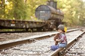 stock photo of railroad car  - Adorable toddler on the railroad tracks dressed as a little hobo - JPG
