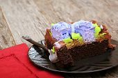 stock photo of chocolate fudge  - Chocolate sheet cake covered with chocolate icing on a plate with a fork - JPG