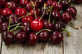 stock photo of black-cherry  - Close up image freshly picked whole black cherries on rustic wood - JPG