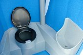 picture of porta-potties  - clean new and unused blue and black portable toilet - JPG