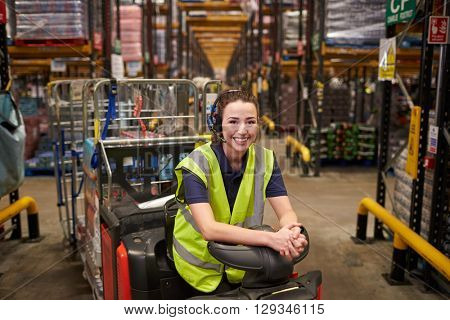 Young woman leaning on tow tractor in distribution warehouse