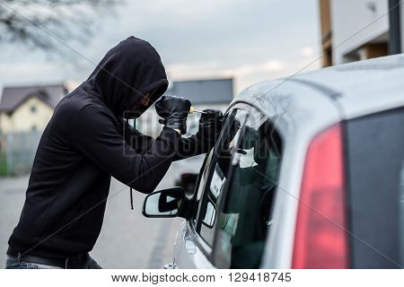 poster of Car Thief Trying To Break Into A Car With A Screwdriver.