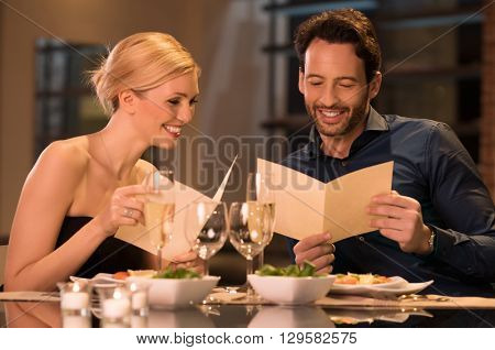 Happy young couple deciding on a dessert from menu card. Smiling couple with menus at luxury restaur