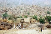 picture of dogon  - A Dogon woman and baby in front of her village at the base of the Bandiagara escarpment in Mali  - JPG