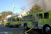 image of firehose  - yellow fire trucks at the scene of a house fire - JPG
