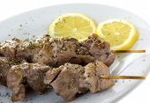 picture of souvlaki  - A plate with two souvlaki and lemons isolated on white background - JPG