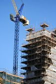 picture of construction crane  - crane and unfinished building surrounded by scaffolding - JPG