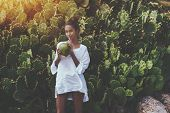 Coquettish Young Cute Brazilian Female In Front Of Quickset Hedge Of Cactuses With Coconut Is Quench poster