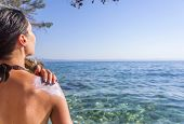 Woman Rubs Sunscreen On His Shoulder. Against The Background Of The Sea. poster