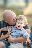 A Happy Baby Boy And A Kissing Him Young Father At Summer Park. A Loving Father Hugging And Kissing  poster