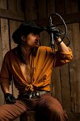 pic of flogging  - Cowboy with Black Leather Flogging Whip in his hand against wooden background - JPG