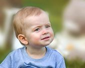 A Close-up Portrait Of A Curious Or Surprised Cute Baby Boy Sitting On Green Grass Outdoor At Summer poster