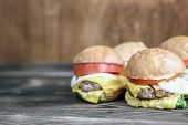 A Burgers On A Wooden Plate. Uicy Burgers Shot Close - Up On Wooden Background. Cheese Spread Over B poster