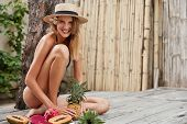 Cute Lovely Female With Slender Legs, Dressed In Swimming Suit And Straw Hat, Sits Near Exotic Fruit poster