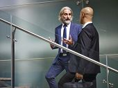 Caucasian And Latino Corporate Executives Having A Conversation While Ascending Stairs In Modern Off poster