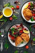 Breaded Chicken Kiev Breast Stuffed With Butter, Garlic And Herbs Served With Vegetables In A Plate poster