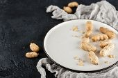 Peanuts In Nutshell On A White Plate With Napkin On Black Background poster