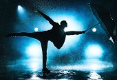 Young strange man dancing with umbrella under the rain. Dramatic blue colors. poster