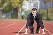 Business Man In Suit Starting And Preparing To Run On The Competition Running Performance Track. poster