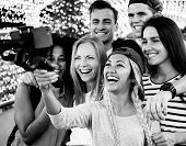 Group of young adult friends taking a group selfie with a selfie stick poster