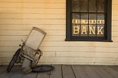 stock photo of antique wheelchair  - Old broken wheel chair leans on the bank porch - JPG