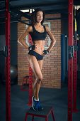 Fit Girl With Black Hair Wearing Black Short Top, Shorts And Gloves Standing On Box In Gym, Brick Wa poster