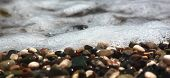 Bright Colorful Stones On The Beach With Clear Clear Water, Foamy Wave, For Banner And Texture. Focu poster