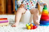 Closeup Of Cute Little 12 Months Old Toddler Baby Girl Child Sitting On Potty. Kid Playing With Educ poster