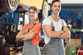 Portrait of two skilled auto mechanics looking at camera with confidence while wearing gray overall  poster