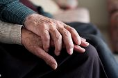 closeup of an old caucasian man and an old caucasian woman sitting in a couch holding hands with aff poster