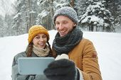 Affectionate guy and girl in winterwear holding smartphone in front of themselves while making selfi poster