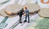 Businessmen Toy Shaking Hands On Cash. Tiny Businessmen Figurines On Money Background. Finance Deal  poster