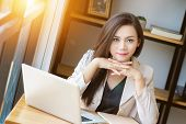 Portrait Of Beautiful And Confident Asian Business Woman In Working Age Using Computer Laptop Techno poster