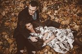 Autumn fashion. Beautiful fashionable couple lying on yellowed autumn grass and leaves. poster