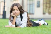 Sad Without A Smile. Sad Schoolgirl Relax On Green Grass. Adorable Little Child With Sad Emotion On  poster